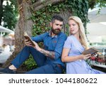 Small photo of Girl with pensive face fall in love with bearded man, couple reads poems. Romantic couple holds old books with poems. Couple in love sit outdoor, nature background. Romantic date concept.