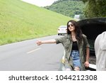 young woman hitchhiking and... | Shutterstock . vector #1044212308