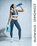 sporty girl drinking water... | Shutterstock . vector #1044244315