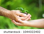 old man and baby holding young... | Shutterstock . vector #1044322402