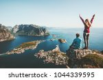 Small photo of Couple family traveling together on cliff edge in Norway man and woman lifestyle concept summer vacations outdoor aerial view Lofoten islands Reinebringen mountain top