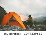 Man traveler relaxing in mountains near of tent camping gear outdoor Travel adventure lifestyle concept hiking active vacations  - stock photo