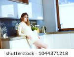 young woman standing in kitchen. | Shutterstock . vector #1044371218