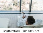 young man lying on sunbed near... | Shutterstock . vector #1044393775