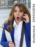 Small photo of Closeup portrait shocked business woman, employee talking on cell phone having unpleasant conversation