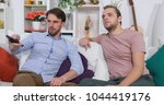 Small photo of Men Entertain in Modern Living Room, Male Zapping the Remote Control Switch Entertainment TV Channels while Sitting on Home Sofa