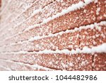 Small photo of Fluffy white snow covers a brown red brick wall in Canadian winter. Photographed at angle. Rows thin and blur as they fade left. Beautiful contrast between soft and rough, natural and man made.