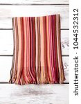 Small photo of Fashionable striped woolen scarf. Vertical colourful stripes. White wooden desks surface background.