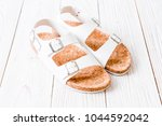 unisex leather sandals on wood...   Shutterstock . vector #1044592042