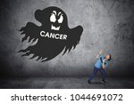 Small photo of Picture of sporty man looks afraid while running away from a ghost with cancer word