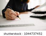hand of businesswoman writing... | Shutterstock . vector #1044737452