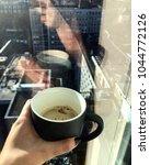cup of coffee held in hand. | Shutterstock . vector #1044772126