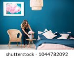 Young Woman Decorating Bedroom...