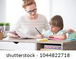 smiling sister helping her... | Shutterstock . vector #1044822718