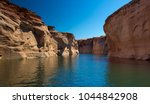View of narrow, cliff-lined canyon from a boat in Glen Canyon National Recreation Area, Lake Powell, Arizona. Antelope Canyon Boat Tours. - stock photo