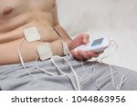Small photo of a man with excess weight makes a stomach massage using an electrical muscle massager