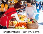 young female buys fruits on... | Shutterstock . vector #1044971596