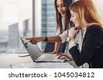 two female coworkers pointing... | Shutterstock . vector #1045034812