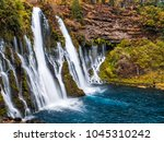 Picturesque waterfall cascade in autumn, surrounded by the moss and yellow bushes. Shot taken in October at McArthur-Burney Falls Memorial State Park, in Shasta County, Northern California.