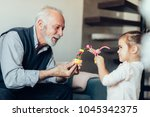 elderly man playing with his... | Shutterstock . vector #1045342375