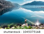 men on the rock over the water... | Shutterstock . vector #1045375168
