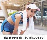 exhausted woman runner taking... | Shutterstock . vector #1045600558