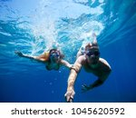 Small photo of Underwater selfie with a stick of young adorable charming adventuristic love student couple swimming and enjoying with goggles in the exotic turquoise sea at summer vacation.