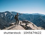 Active female hiker with rucksack using smartphone for shooting video for travel blogg standing on mountain top, girl wanderlust making picture via cellphone on scenic landscape enjoying weekend trip - stock photo