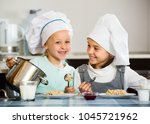 two positive small girls eating ... | Shutterstock . vector #1045721962