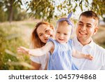happy mom and dad hold little... | Shutterstock . vector #1045794868