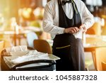 waiter preparing the table with ... | Shutterstock . vector #1045887328