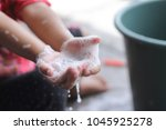 cute girl washing her hand and... | Shutterstock . vector #1045925278