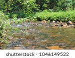 """Small photo of A bright landscape with the insipid water of a mountain river in the Urals. National park """"Taganay"""" Chelyabinsk region"""
