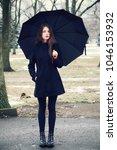 girl with umbrella walking in... | Shutterstock . vector #1046153932