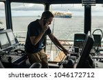 Small photo of Deck navigation officer on the navigation bridge. He speaks by VHF radio, GMDSS Watchkeeping, collision prevention at sea. COLREG