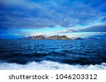 Small photo of Beautiful scenic view, distant arctic land with rugged rocks covered with snow and moss at the background of dramatic blue sky in Bellsund, Spitsbergen (Svalbard island), Norway, Greenland Sea