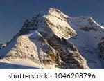 towering snowy monarch peak on... | Shutterstock . vector #1046208796