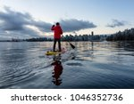 Small photo of Adventurous male is paddle boarding near Stanley Park with Downtown City Skyline in the background