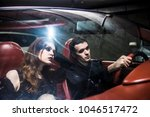 Small photo of sad and brutal dreaming Young Couple Sitting In cabrio Car with leather interior. man sulk on melancholy pissed woman in luxury auto. night scene. car underground parking