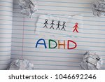 Small photo of ADHD. Abbreviation ADHD on notebook sheet with some crumpled paper balls on it. Close up. ADHD is Attention deficit hyperactivity disorder.