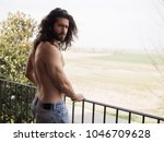 man with long hair on a roof | Shutterstock . vector #1046709628