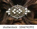 Small photo of Pearl and filagree hair clasp in beautiful long reddish brown hair - close up