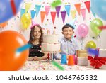 Small photo of Little boy and a little girl with party hats and a cake celebrating a birthday