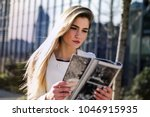 young woman reading a magazine  | Shutterstock . vector #1046915935