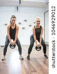 two sportswomen doing squat... | Shutterstock . vector #1046929012