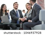 two colleagues handshaking... | Shutterstock . vector #1046937928