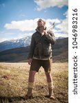 Small photo of One handsome strong stylish male logger of young man holding wooden axe in forest outdoor and mountains in the background