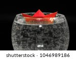 paper boat in a glass of...   Shutterstock . vector #1046989186