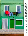 colorful house in burano island ... | Shutterstock . vector #1047056938
