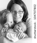 Young mother and her children. Close up with shallow DOF. - stock photo